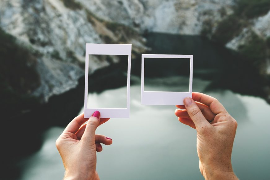 two people holding up polaroid frames to a landscape