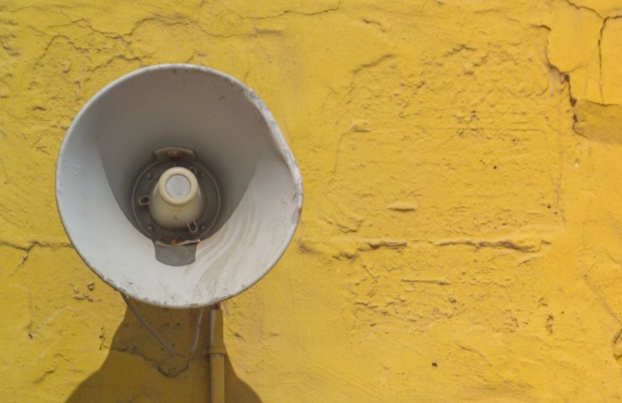 megaphone on yellow wall