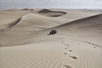 4x4 driving across sand dunes in the desert