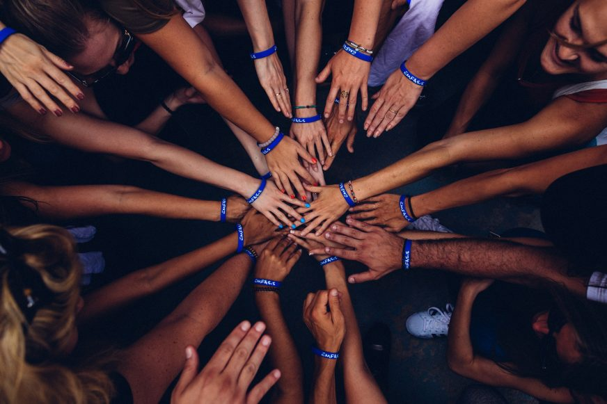 group of people with hands in middle