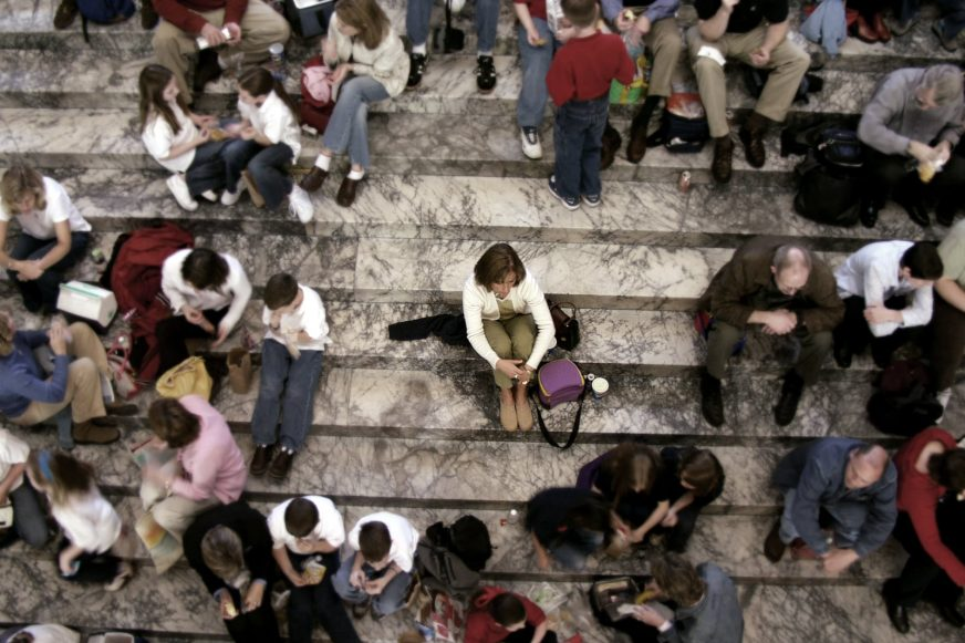 Woman sat on steps surrounded by people but sat alone