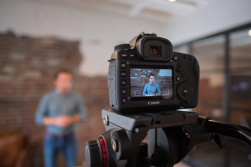 camera on a tripod filming a man