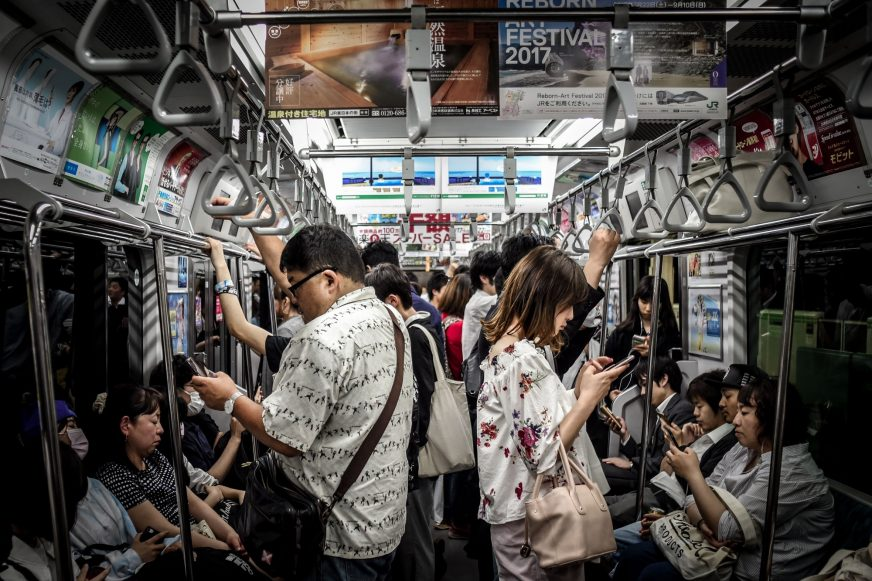people using phones on a train
