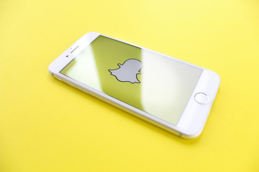 A mobile phone with the snapchat logo on the screen
